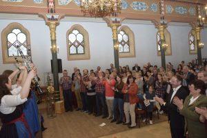 Die Zuschauer applaudieren am Ende des Konzerts, während die Klarischnättra freudig ihre Instrumente in die Höhe strecken.